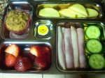 nitrate free ham, cucumber cheese bites, apple nut butter sandwiches, strawberries, homemade almond flour muffin, sticker for treat